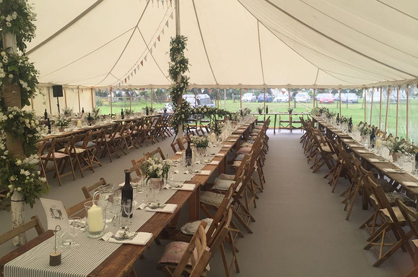 Tables and chairs set up inside marquee for a wedding