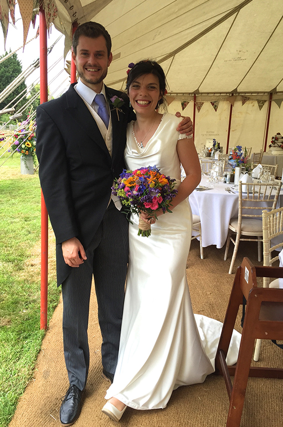 Smiling wedding couple inside a marquee